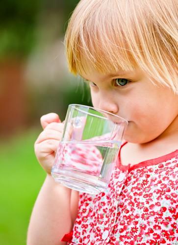 Little Girl Drinks Water Outside in Summer